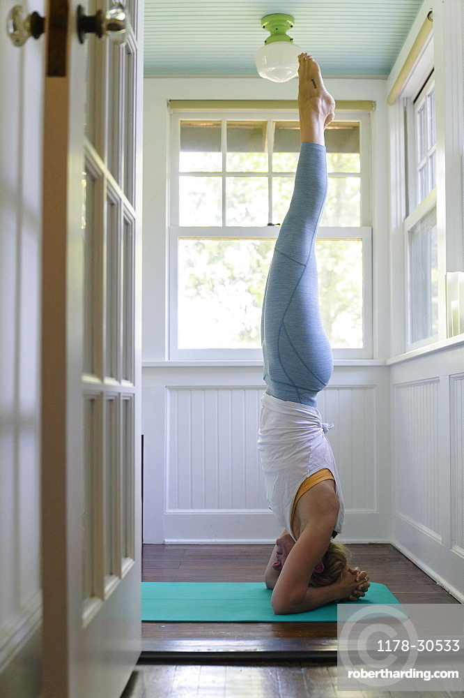 Woman doing headstand on mat
