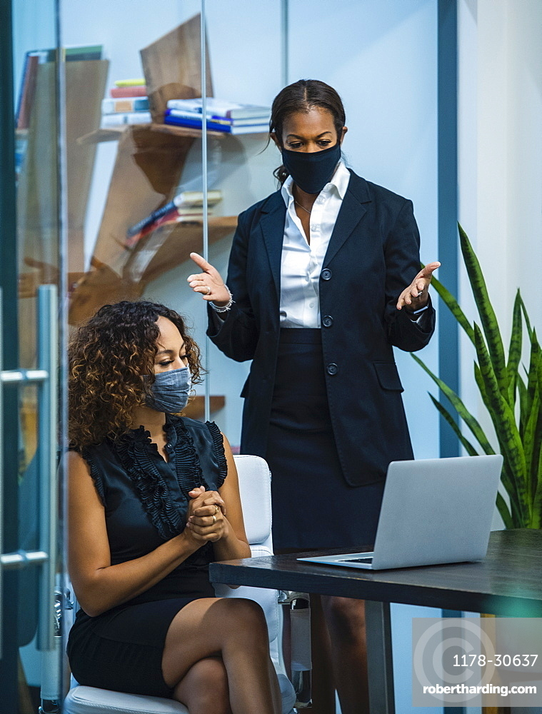 Two businesswomen wearing face masks working on laptop at desk in office