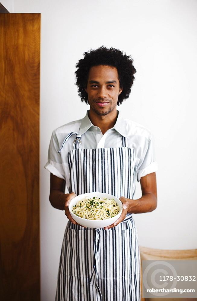 Mixed race man holding bowl of pasta