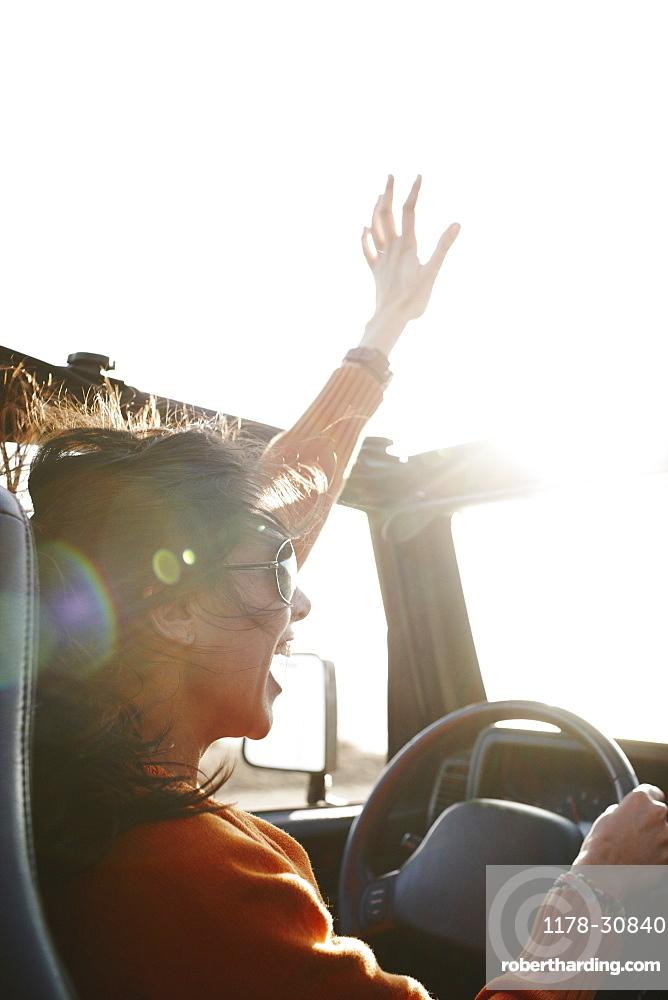 Hispanic woman raising arms while driving