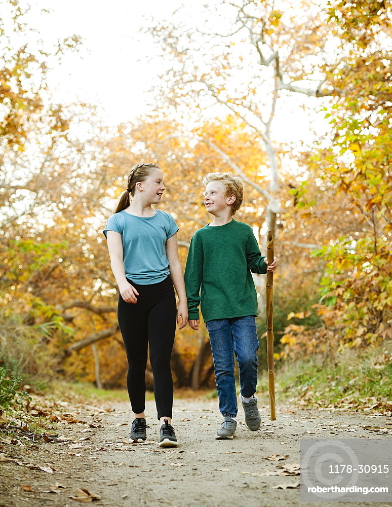 United States, California, Mission Viejo, Boy (10-11) and girl (12-13) walking on footpath in forest
