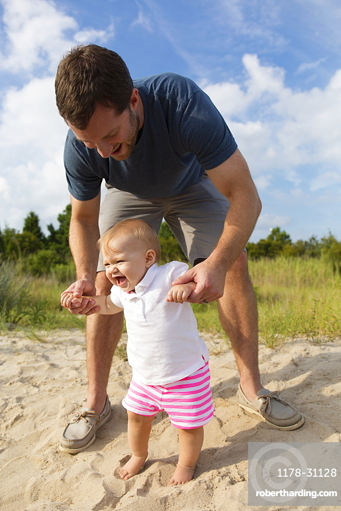 Mid adult man holding baby daughters hands while toddling in sand