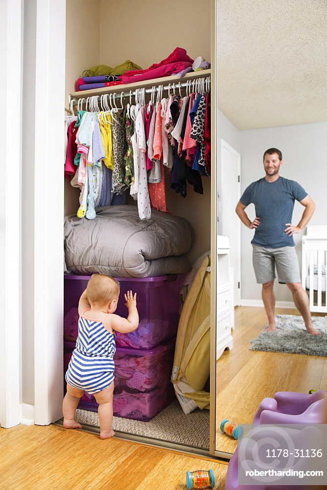 Mid adult man watching baby daughter search box in wardrobe