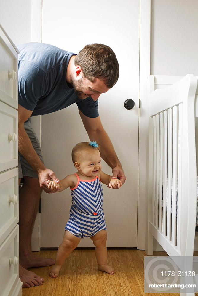 Mid adult man holding baby daughter hands whilst toddling in nursery
