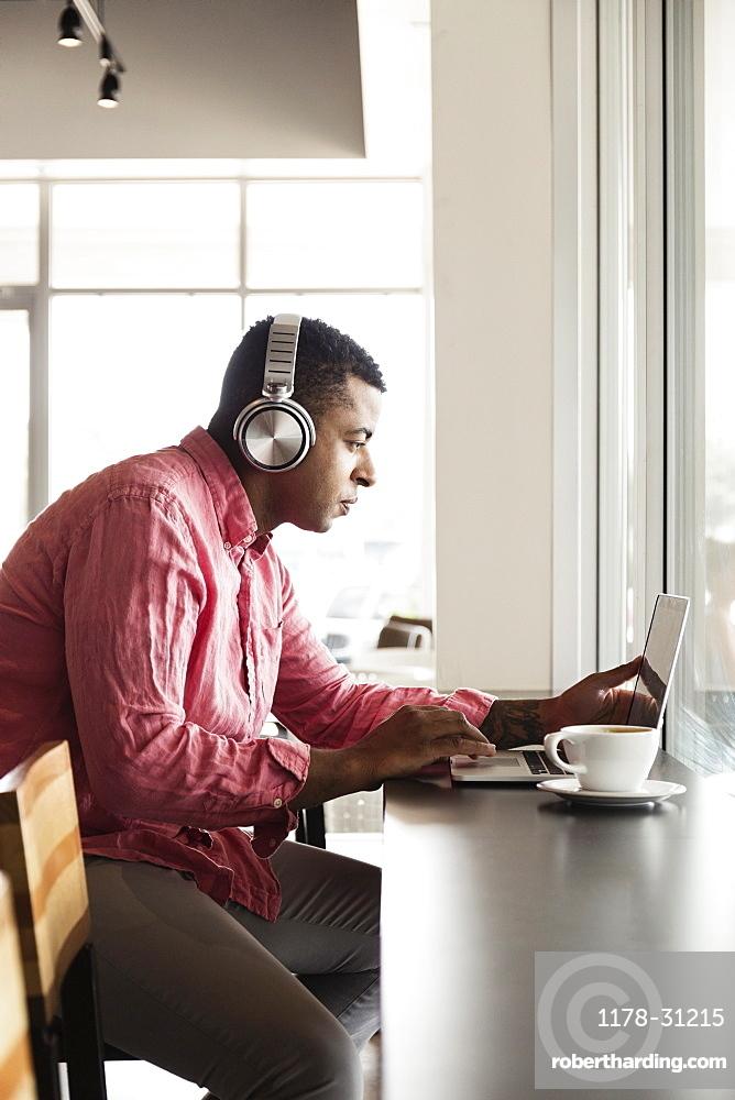 Young man in coffee shop, wearing headphones, using laptop