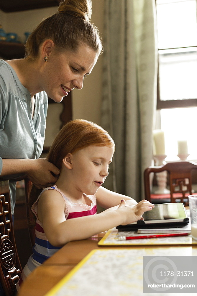 Girl using digital tablet at dining room table whilst mother styling her hair