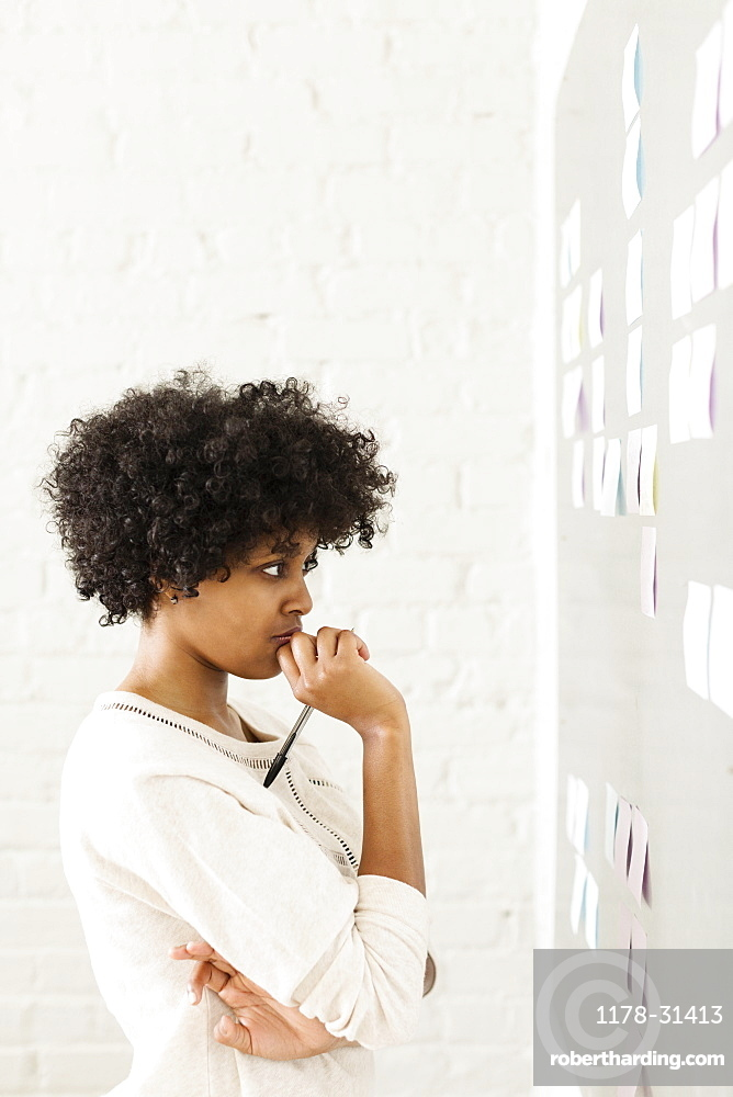 Young woman reading adhesive notes on wall
