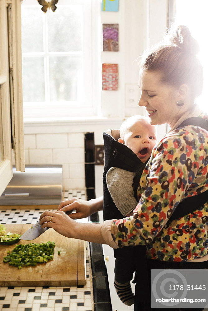 Mid adult mother preparing food with baby son in sling