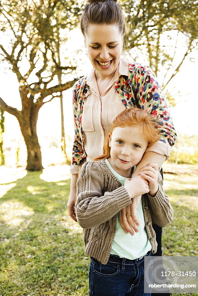 Portrait of mid adult mother with arm around daughter in park
