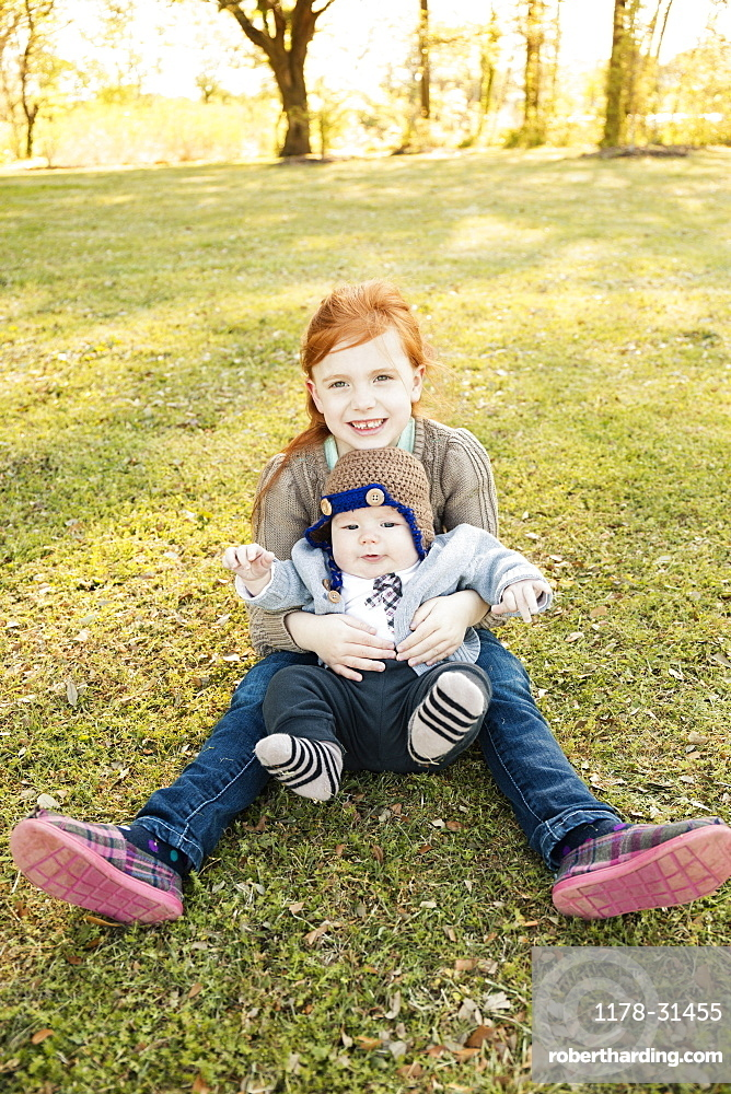 Portrait of girl and baby brother on grass in park
