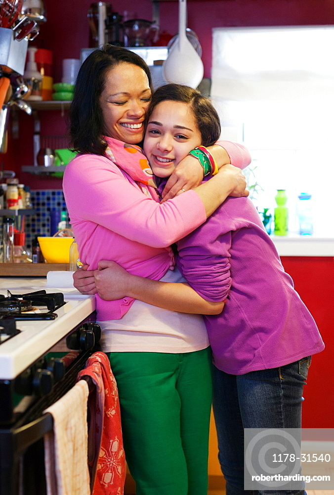 Portrait of mother hugging daughter in kitchen