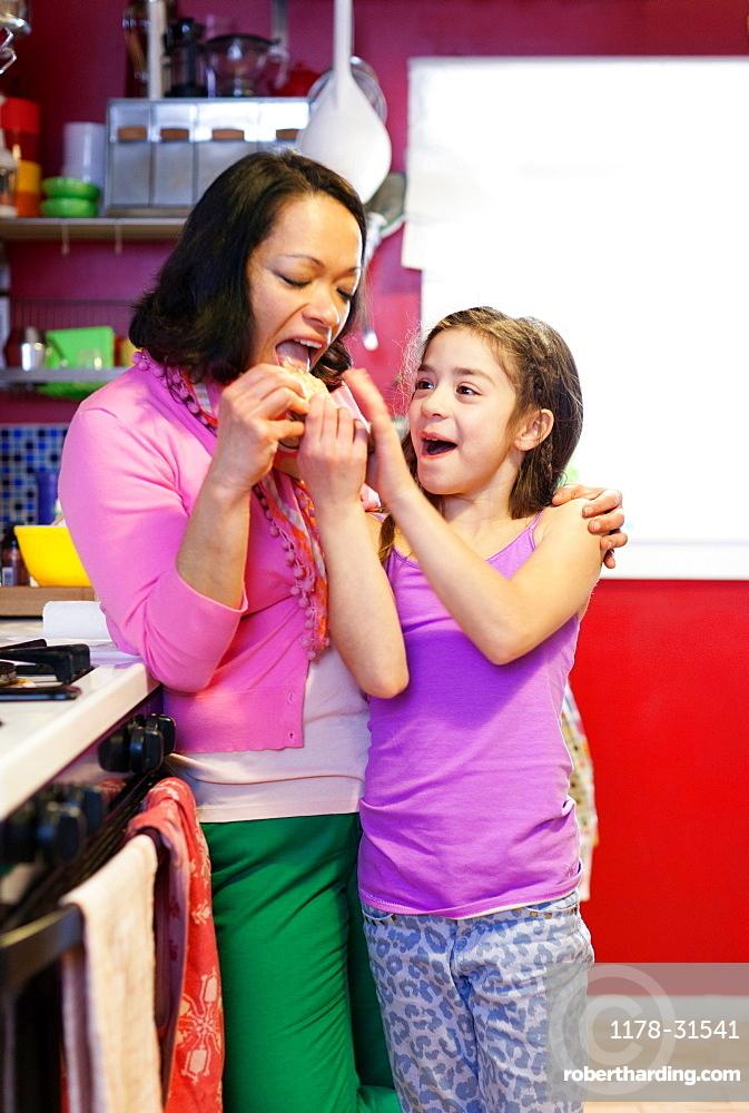 Daughter feeding mother cracker in kitchen