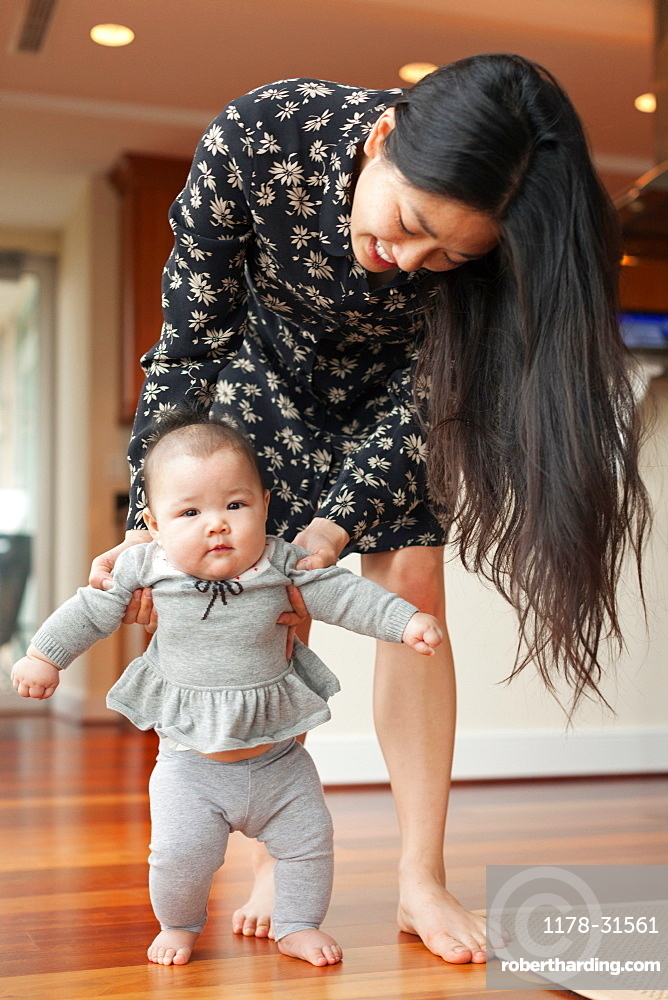 Mother helping baby girl to walk