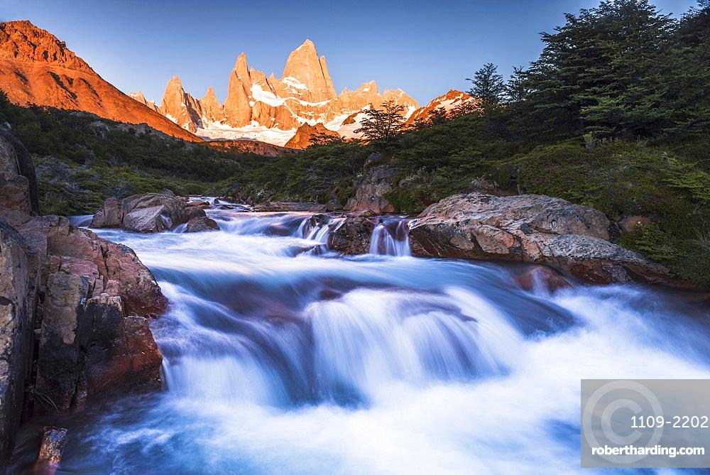 Sunrise Mount Fitz Roy (Cerro Chalten) and waterfall seen on Lago de los Tres hike, UNESCO World Heritage Site, El Chalten, Patagonia, Argentina, South America