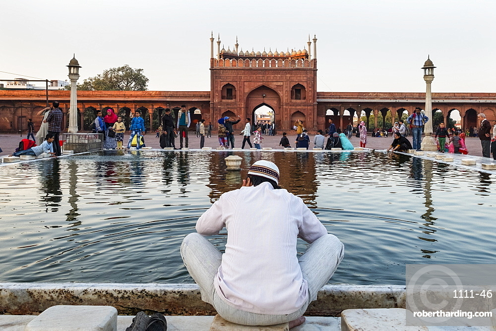 Muslim man washing hands and feet before prayer time, Jama Masjid, one of the largest mosques in India, South Asia