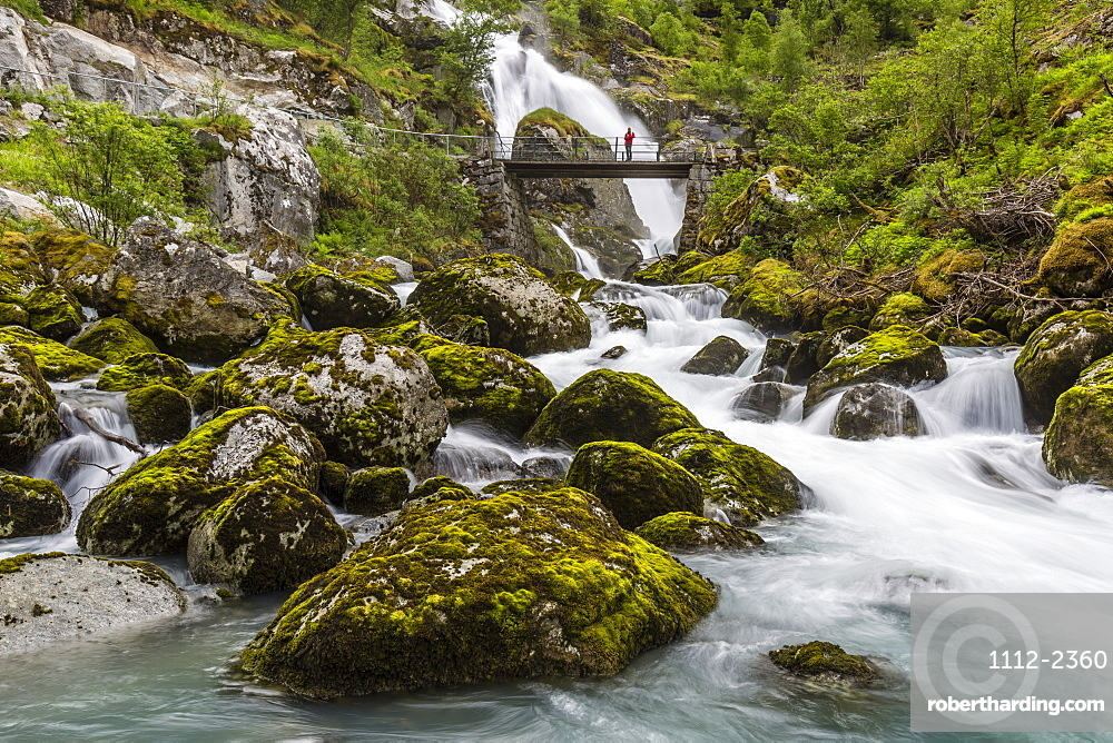 Slow shutter speed silky water of the Olden River and bridge as it flows along Briksdalen, Olden, Nordfjord, Norway, Scandinavia, Europe