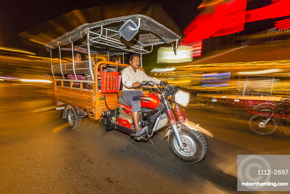 Night photograph of tuk-tuk and driver in the capital city of Phnom Penh, Cambodia, Indochina, Southeast Asia, Asia