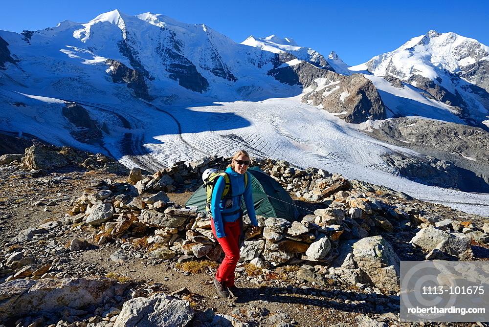 Woman hiking with view to Piz Palue (3905 m), Bellavista (3922 m), Piz Bernina (4049 m) and Pers glacier, Engadin, Grisons, Swit