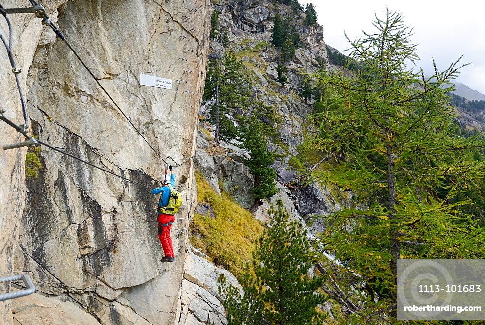Woman climbing the via ferrata La Resgia, Engadin, Grisons, Switzerland