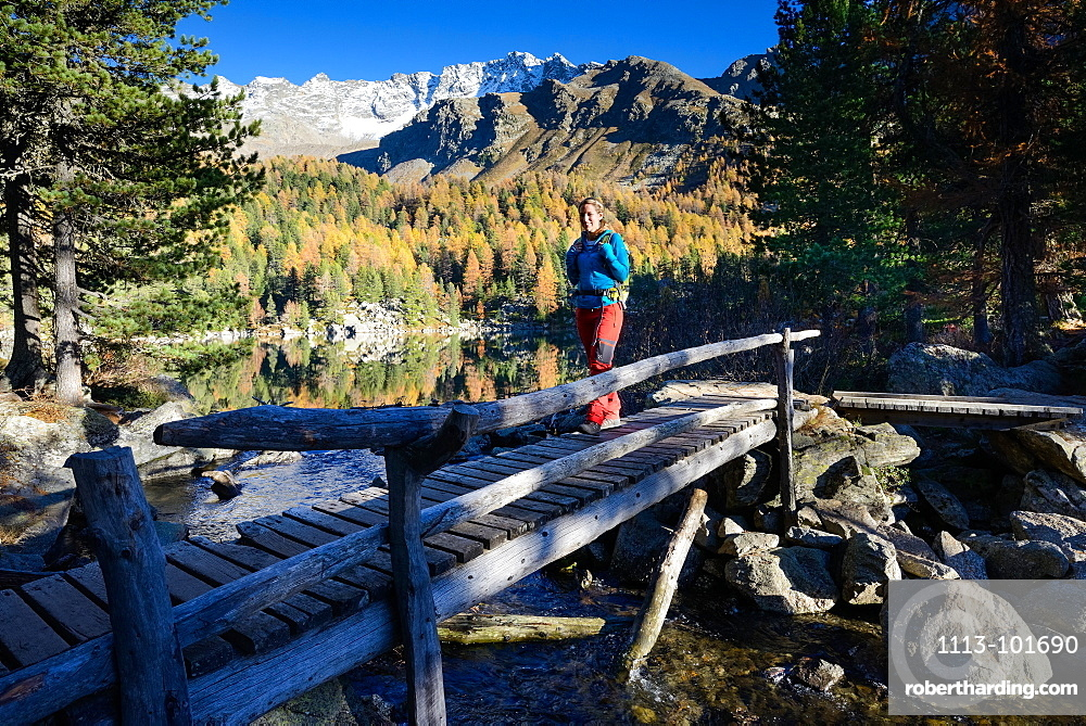 Woman hiking along the shore of lake Saoseo (2028 m) with Scima di Saoseo (3264 m), Valposchiavo, Grisons, Switzerland
