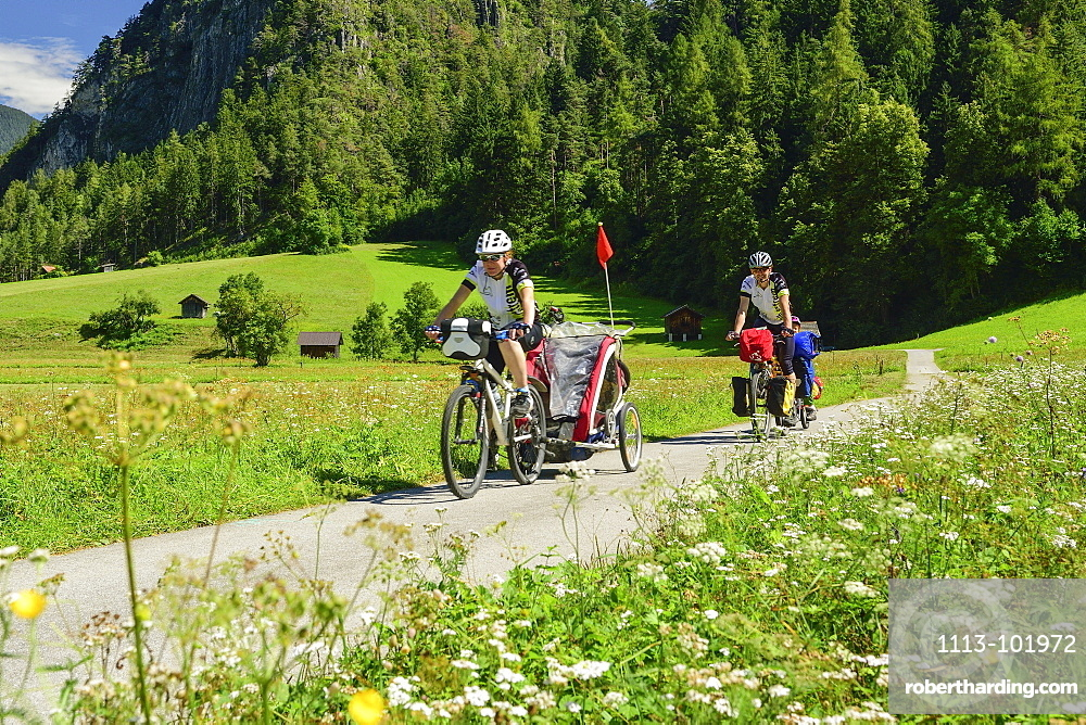 Two cyclists with child trailer riding along Inn cycle route, Zams, Tyrol, Austria