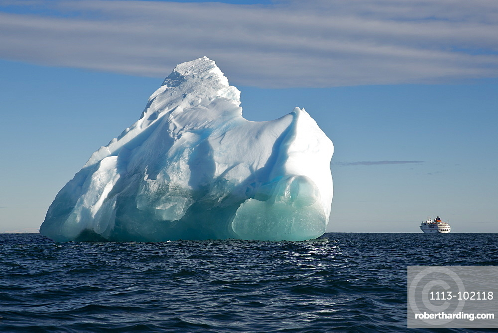 Iceberg in bright sunlight with expedition cruise ship MS Hanseatic (Hapag-Lloyd Cruises) in the background, Bird Point, Ross Is