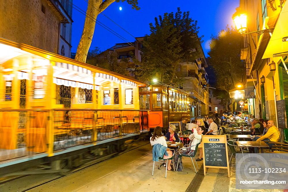 historical tram driving between Port de Soller and Palma de Mallorca in the evening, guests in restaurants, Serra de Tramuntana, Soller, Majorca, Balearic Islands, Spain, Europe