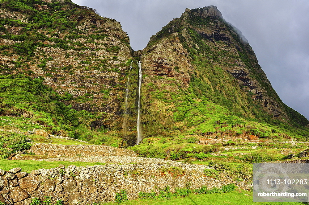 Waterfall Poco do Bacalhau, mountains and abandoned stone houses, Faja Grande, Island of Flores, Azores, Portugal, Europe, Atlantic Ocean