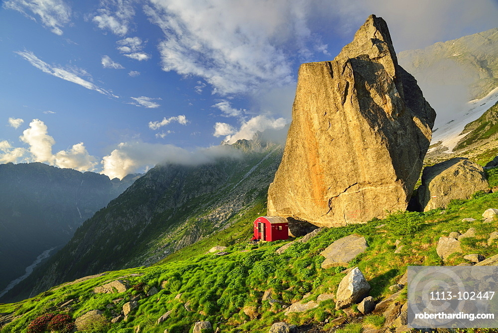 Red bivouac beneath boulder, Lombardy, Italy