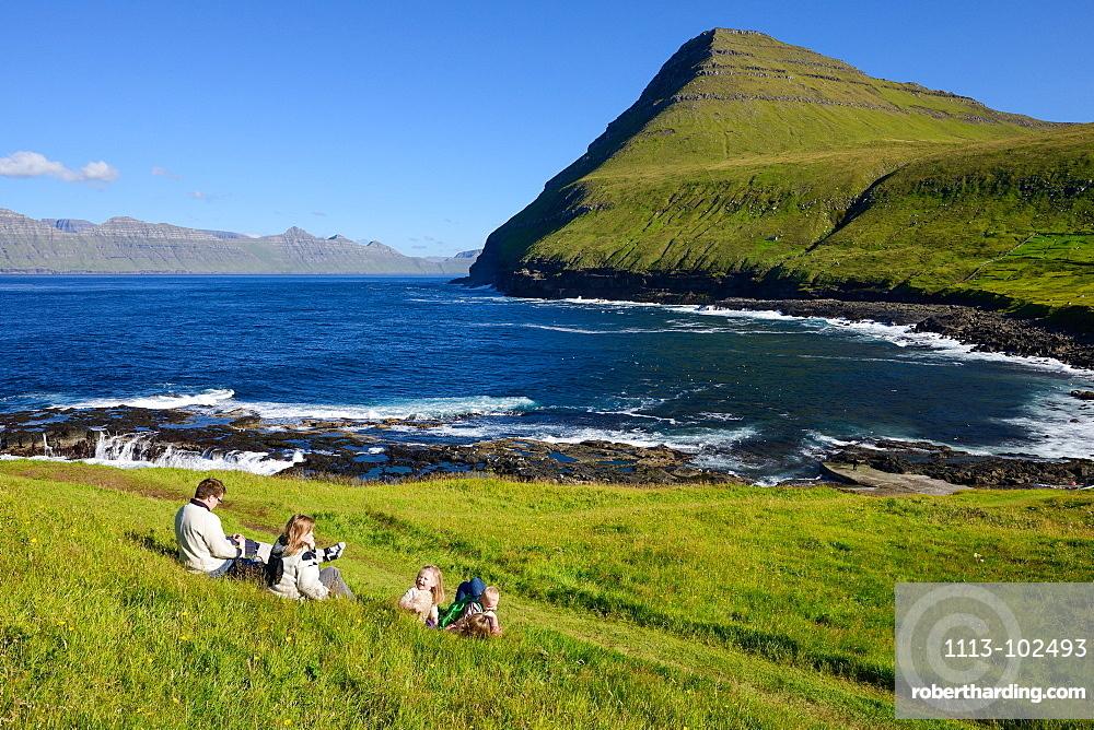 Family sitting on the grass overlooking the bay of Gjogv, Eysturoy Island, Faroe Islands