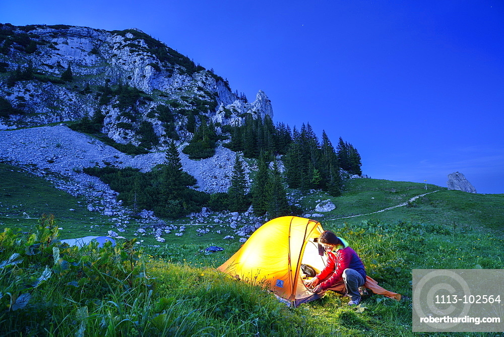 Woman in front of a tent, Rossstein, Bavarian Prealps, Upper Bavaria, Bavaria, Germany