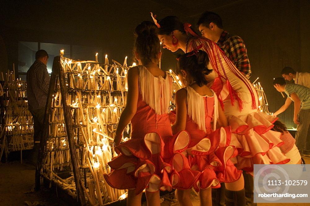 Pilgrims lightning candles at night opposite the church Eremita del Rocio at El Rocio at Pentecost, Huelva, Andalusien, Spanien