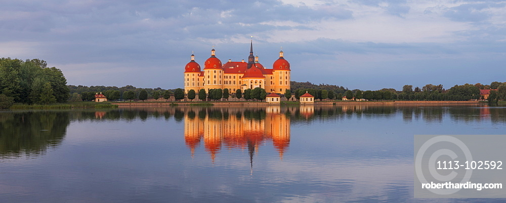 Panorama of the baroque Moritzburg castle in the evening sun with its reflection in the castle pond, near Dresden, Saxony, Germany