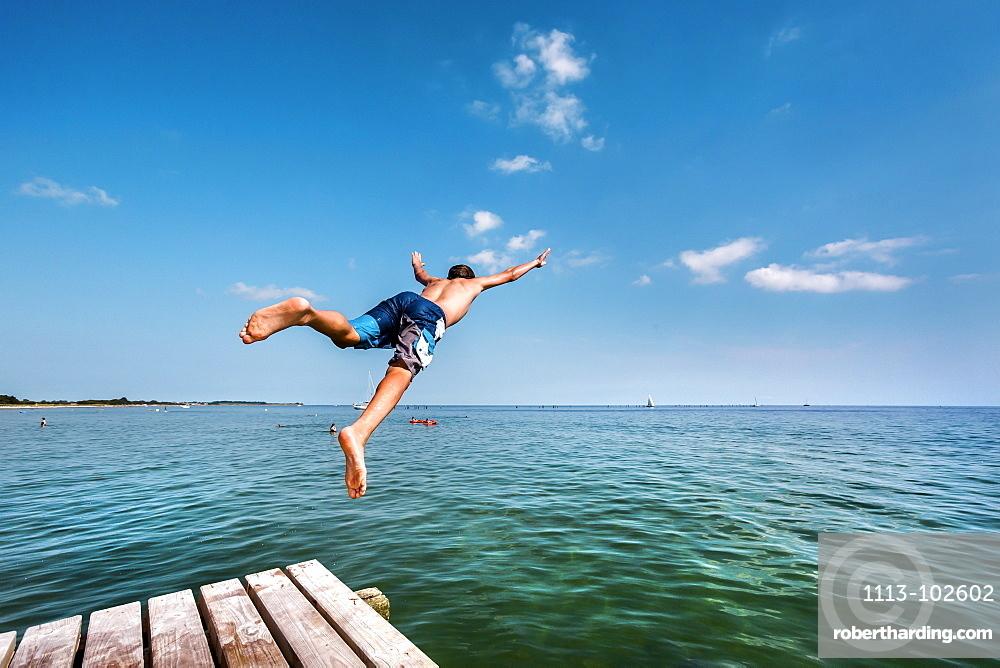 Boy diving from a pier, South beach, Burgtiefe, Fehmarn island, Baltic Coast, Schleswig-Holstein, Germany