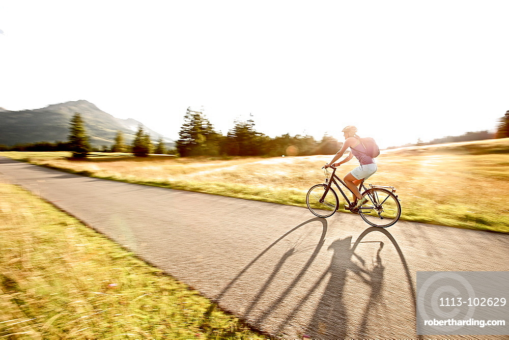 Young woman riding her bike on a sunny day, Tannheimer Tal, Tyrol, Austria