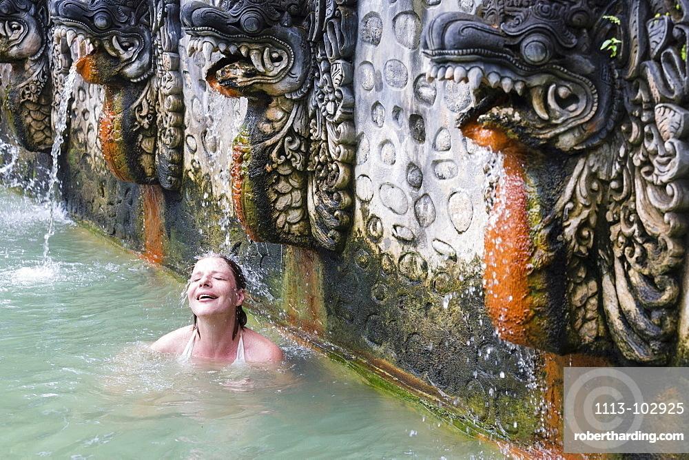 Female tourist bathing in hot spring air panas, Banjar Tegeha, Buleleng, Bali, Indonesia