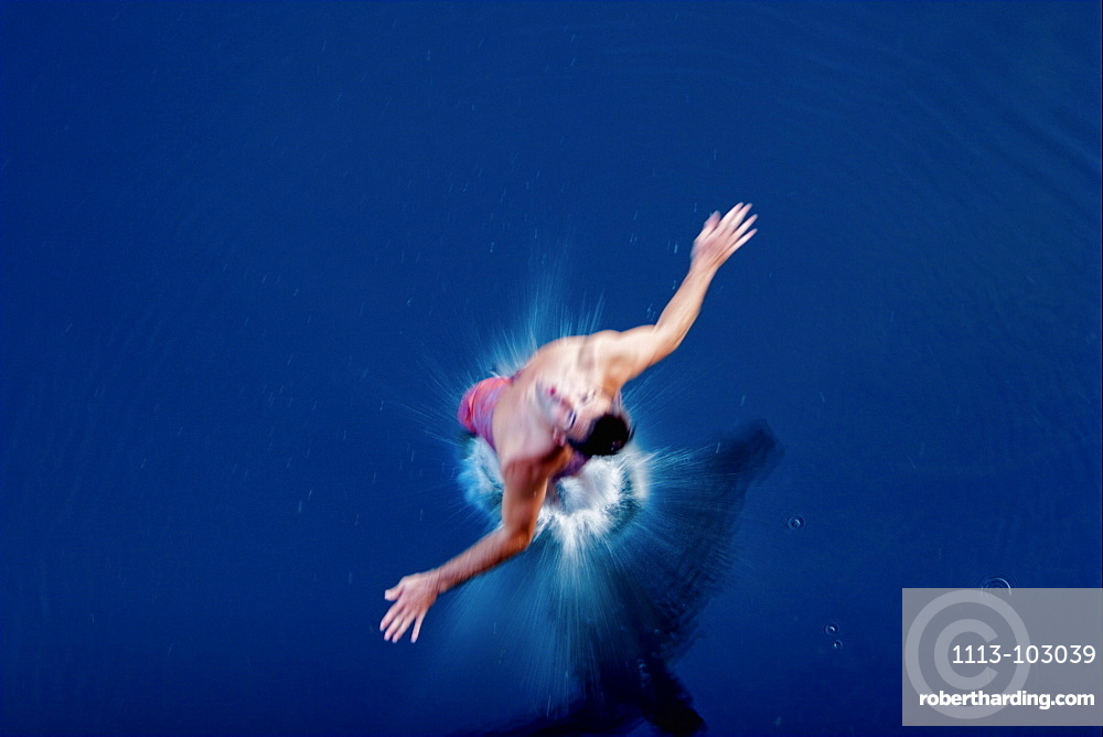Young man jumping into the water, Fuessen, Bavaria, Germany
