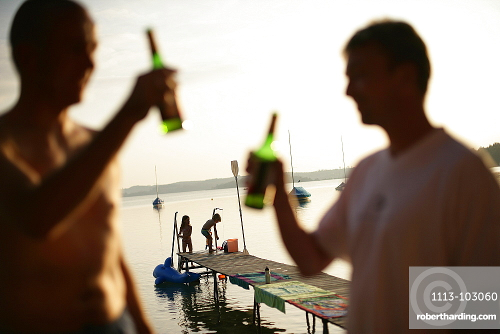 Two men drinking bottles of beer, children playing on jetty in background, Lake Woerthsee, Bavaria, Germany, MR