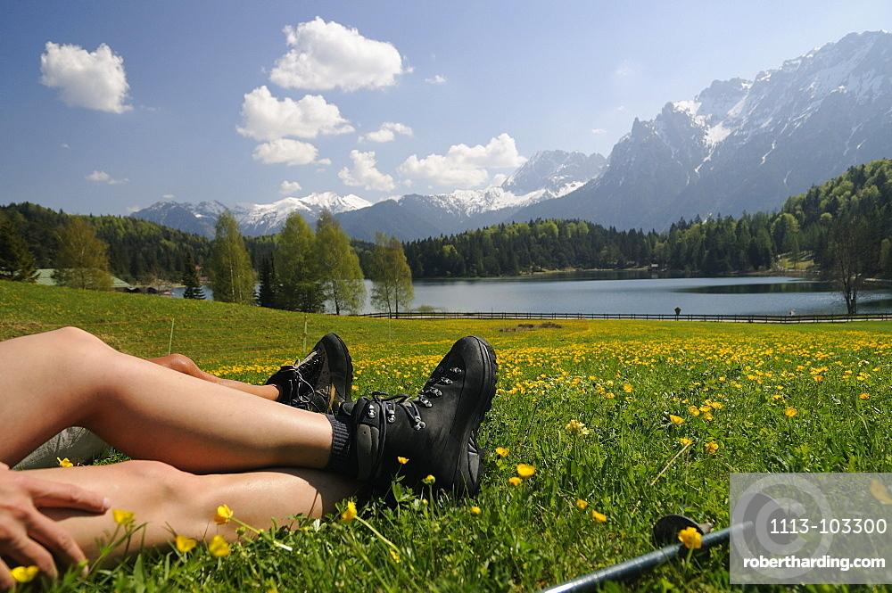 Couple hiking at Lautersee, having a rest, Mittenwald, View towards Karwendel Mountain Range, Upper Bavaria, Bavaria, Germany, Europe