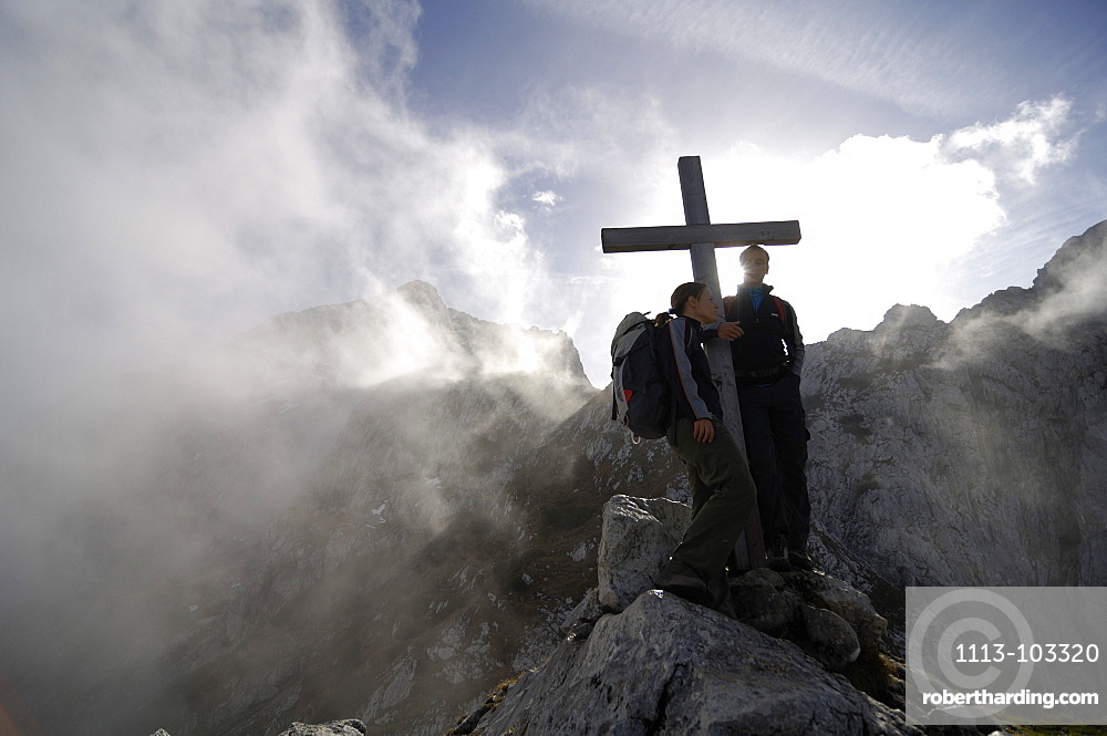 Hikers at a summit cross amidst some clouds, Wetterstein, Bavaria, Germany, Europe