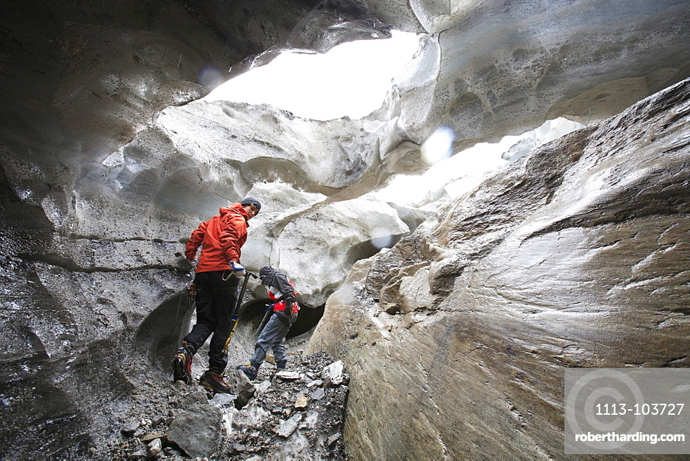 Two women inside a glacier cave, Brunegg Glacier, Canton of Valais, Switzerland, MR