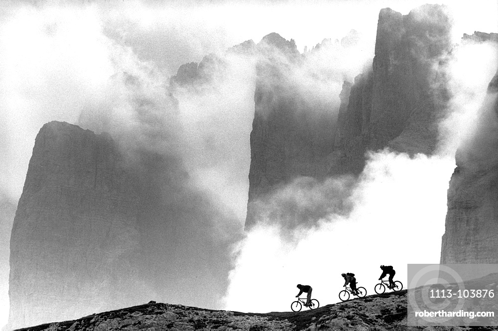 Three male mountain bikers on the way, Dolomites, Italy