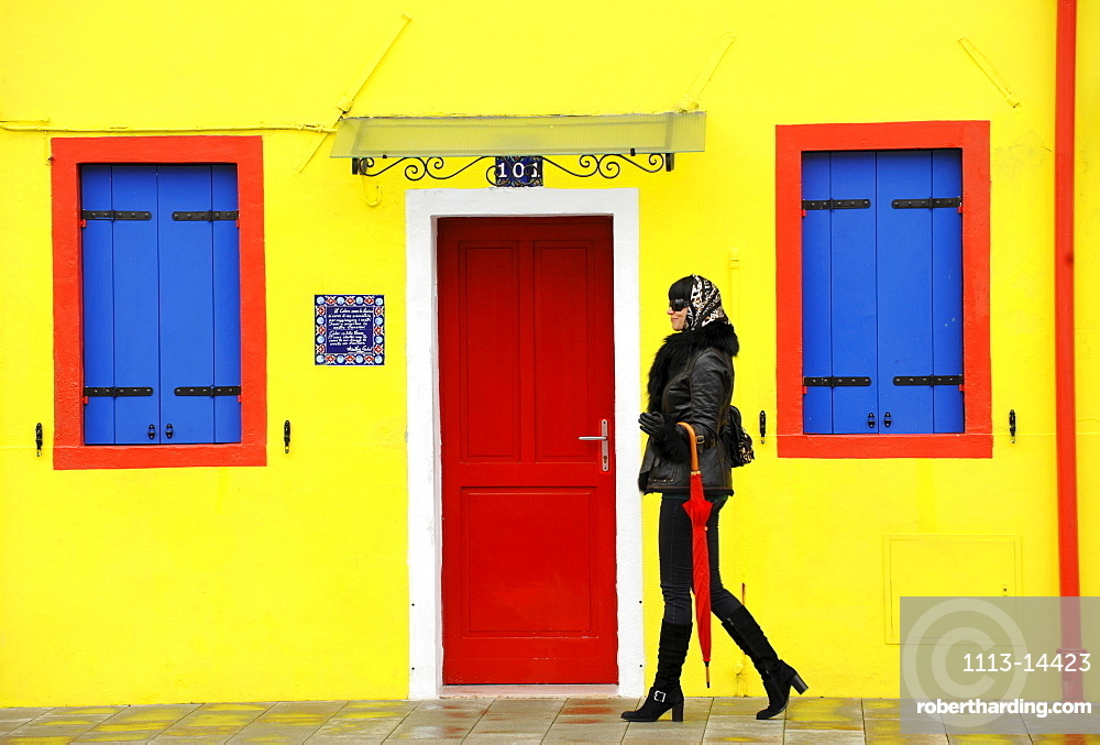 Young woman walking along the street, Burano, Venice, Veneto, Italy