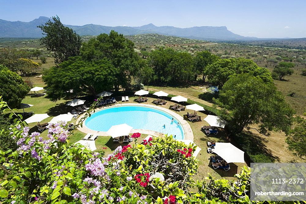 View over swimming pool of Taita Hills Lodge, Taita hills in background, Coast, Kenya