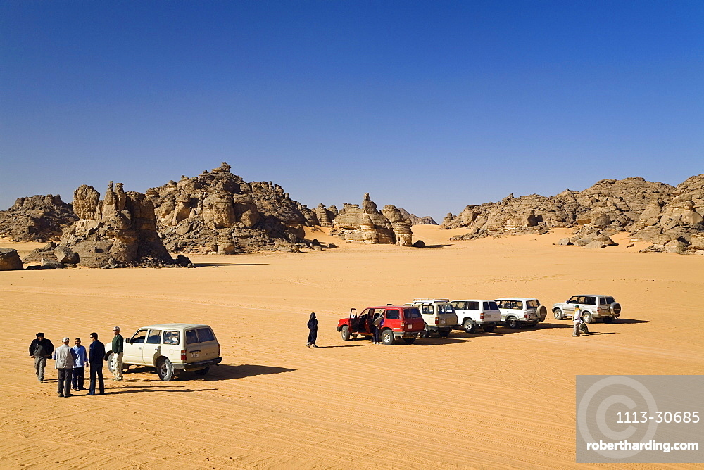 Jeeps and tourists in stony desert, Akakus mountains, Libya, Sahara, North Africa
