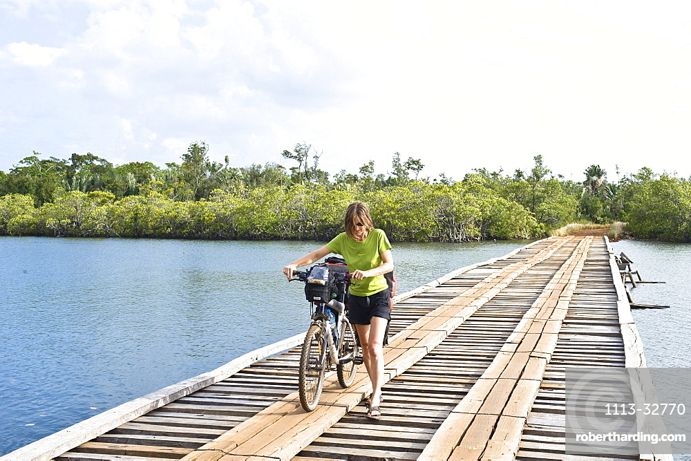 Woman is pushing her mountainbike in the masoala national park in madagaskar, africa