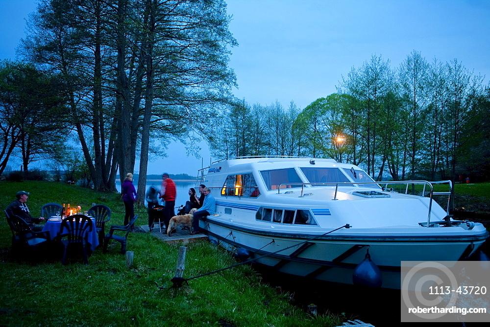People having a barbeque on the banks of lake Ellbogensee, Houseboat, near Fuerstenberg/Havel, Mecklenburg Lake District, Mecklenburg-Pomerania, Germany