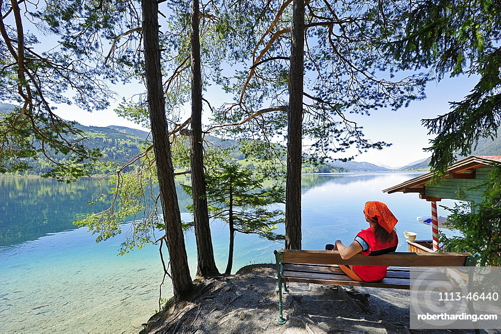 Woman sitting on wooden bench and enjoying view of lake Weissensee, lake Weissensee, Carinthia, Austria, Europe