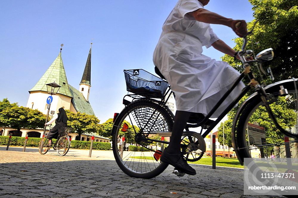 Cyclists at suqare Kapellplatz, Altoetting, Bavaria, Germany, Europe