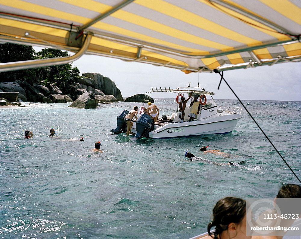 People snorkeling off tiny Coco Island, La Digue and Inner Islands, Republic of Seychelles, Indian Ocean